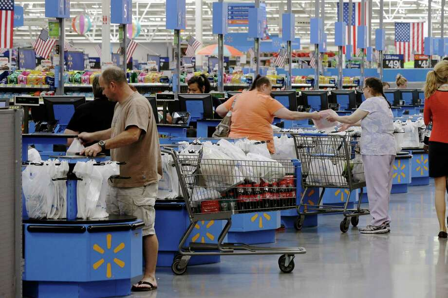 Shoppers check out at a Wal-Mart Supercenter in Springdale, Ark. U.S. retail sales rose 0.2 percent to $448 billion last month, the Commerce Department said. Photo: Danny Johnston, STF / AP