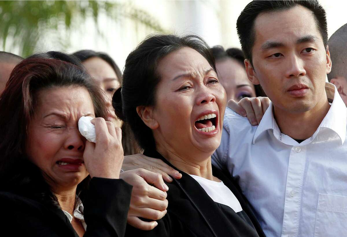 Trung Do Nguyen, right, comforts his mother, Van Thanh Nguyen, at a wake for his sister and her daughter, Tin Nguyen, at the Peek Funeral home in Westminster, Calif., on Friday, Dec. 11, 2015. Nguyen died in the mass shootings in San Bernardino, Calif., last Wednesday, Dec. 2. Woman at left is unidentified.(AP Photo/Nick Ut) ORG XMIT: LA105