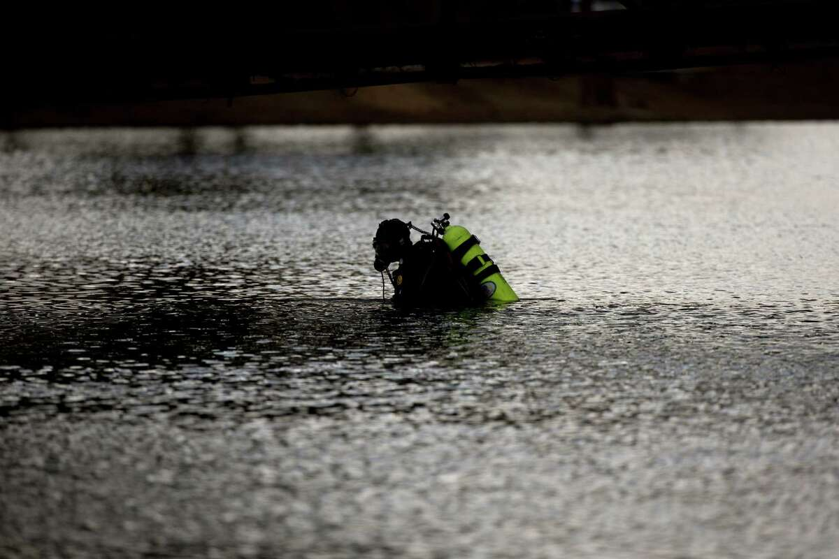 A member of the FBI dive team searches Seccombe Lake Friday, Dec. 11, 2015, in San Bernardino, Calif., for evidence in connection with last week's fatal shooting at Inland Regional Center, The FBI says divers are searching the lake because leads indicate the shooters who killed 14 people at a holiday party had been in the area. (AP Photo/Jae C. Hong) ORG XMIT: CAJH116