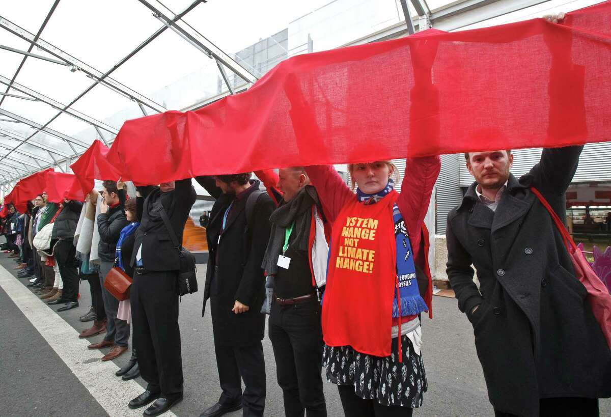 Climate activists carry a red banner during a demonstration at the COP21, United Nations Climate Change Conference, in Le Bourget, north of Paris, Friday, Dec. 11, 2015. Hundreds of climate activists have stretched a block-long red banner through the Paris climate talks to symbolize