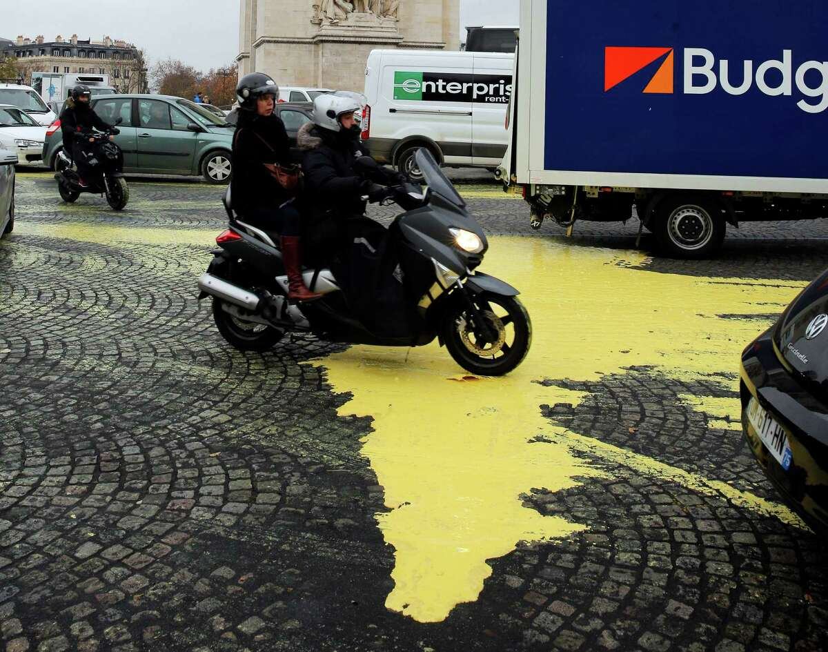 Yellow paint is poured on the street during a protest by activists from environmental group Greenpeace on the Champs-Elysee in Paris, Friday, Dec. 11, 2015 The protest is one of many activist actions linked to the COP21, the United Nations Climate Change Conference. (AP Photo/Christophe Ena) ORG XMIT: XCE103