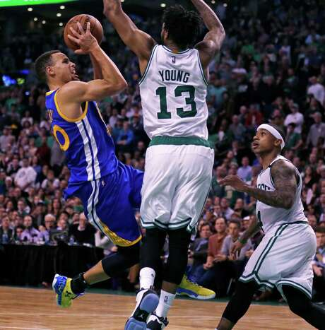 Warriors guard Stephen Curry shoots over Celtics guard James Young (13) during Friday night's game in Boston. Curry finished with a game-high 38 points. Photo: Charles Krupa, STF / AP