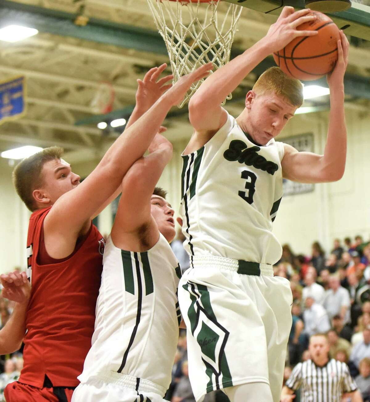 Shen's Kevin Huerter, right, wins the rebound over teammate Mike Pizziketti, center, and Guilderland's Andrew Sischo during their basketball game on Friday, Dec. 11, 2015, at Shenendehowa High in Clifton Park, N.Y. (Cindy Schultz / Times Union)
