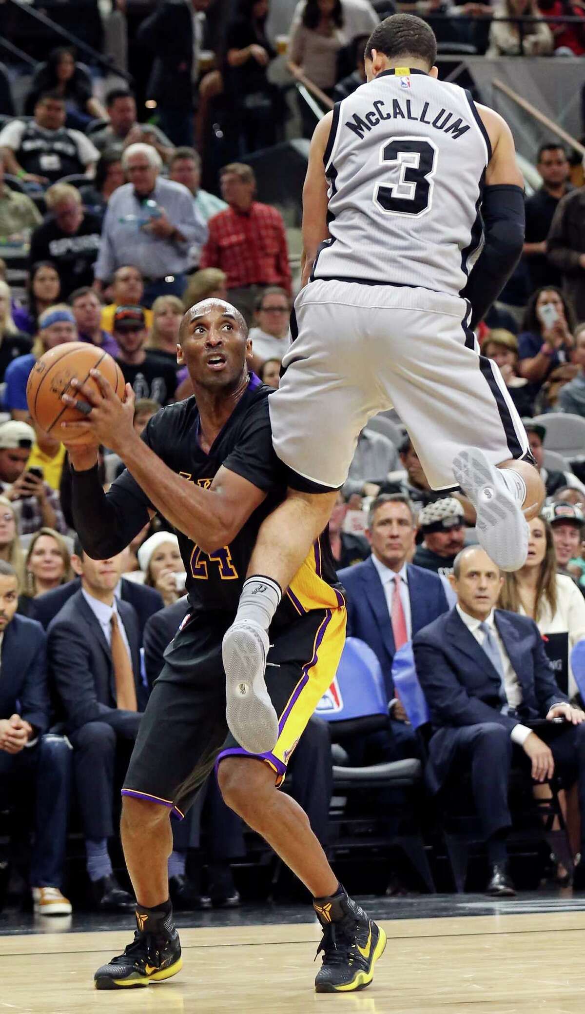 Los Angeles Lakers' Kobe Bryant is fouled by San Antonio Spurs' Ray McCallum during second half action Friday Dec. 11, 2015 at the AT&T Center.