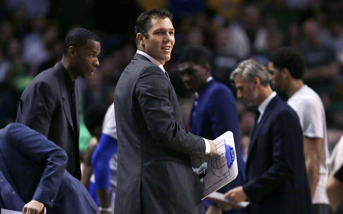 Golden State Warriors interim head coach Luke Walton smiles as he walks back to the bench after a time out during the first quarter of an NBA basketball game against the Boston Celtics in Boston, Friday, Dec. 11, 2015. (AP Photo/Charles Krupa)