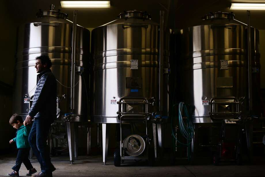 Lichen Estate assistant winemaker Dan Rivin, with his 3-year-old son Calder Rivin, stroll by a row of stainless steel tanks at the winery. Photo: Erik Castro, Special To The Chronicle