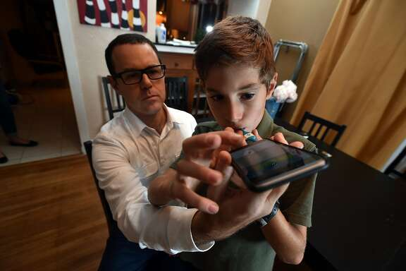 "Dr. Michael Greenberg (L) demonstrates how to use his ""smart"" thermometer on his son Sam Greenberg (R) at their home in Berkeley, California on Friday, December 11, 2015. Kinsa Health makes the device which uses an app to track temperatures and other symptoms to help identify outbreaks of the flu or other ailments."