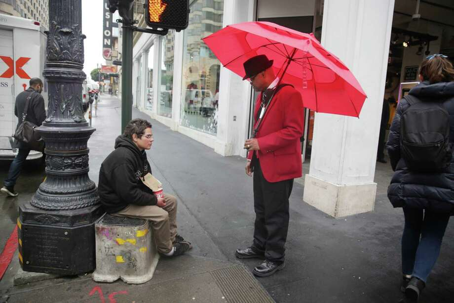 Wayne Alexis (right), Union Square ambassador, talks with Alex Ceffalo (left), who is homeless, at the corner of Powell and Ellis Streets  as Ceffalo sits on the corner on Wednesday, December 9,  2015 in San Francisco, Calif. Photo: Lea Suzuki / The Chronicle / ONLINE_YES