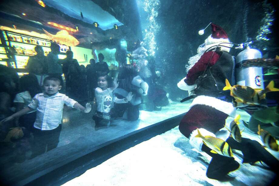 Children peer into the tank as Andrew Sanders poses for photos as Santa at the Downtown Aquarium during Breakfast with Santa on Saturday, Dec. 12, 2015, in Houston. Santa will be featured in the water for photos in the aquarium, along with live music, activities and a breakfast buffet December 17– 24 from 8am – 10am. Photo: Brett Coomer, Houston Chronicle / © 2015 Houston Chronicle