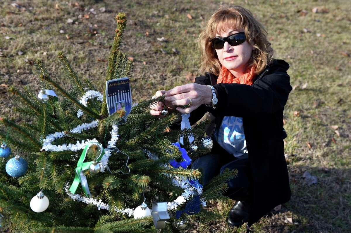 Colette Torri of Niskayuna decorates a tree planted in memory of a victim of the Sandy Hook Elementary School shooting on Saturday, Dec. 12, 2015, at Sandy Hill Memorial Park in Wilton, N.Y. Moms Demand Action gathered to honor the 26 victims who died in the deadly mass shooting at the Sandy Hook Elementary School in Newtown, Conn. three years ago. (Cindy Schultz / Times Union)