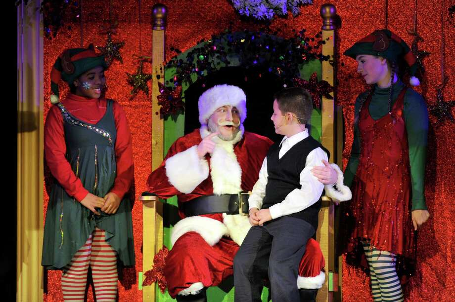 Kris Kringle, played by Patrick Hayes, promises Jimmy, played by Sean Hugh Keeney, a Christmas present during the Trinity Catholic High School Crusader Players production of Miracle on 34th St. on Saturday, Dec. 12, 2015. Photo: Michael Cummo, Hearst Connecticut Media / Stamford Advocate