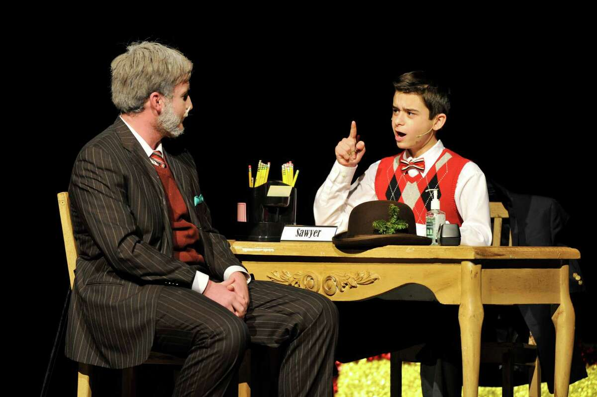 Evan Guerrera, as Mr. Sawyer, sits down to question Patrick Hayes, as Kris Kringle, during the Trinity Catholic High School Crusader Players production of Miracle on 34th St. on Saturday, Dec. 12, 2015.