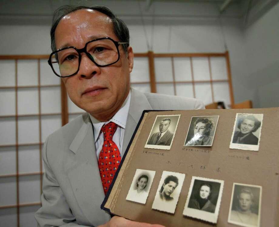 Akira Kitade holds a photo album that belonged to Tatsuo, Osako, a former colleague at the Japanese tourism bureau who helped Jewish refugees. Photo: Shizuo Kambayashi /Associated Press / AP