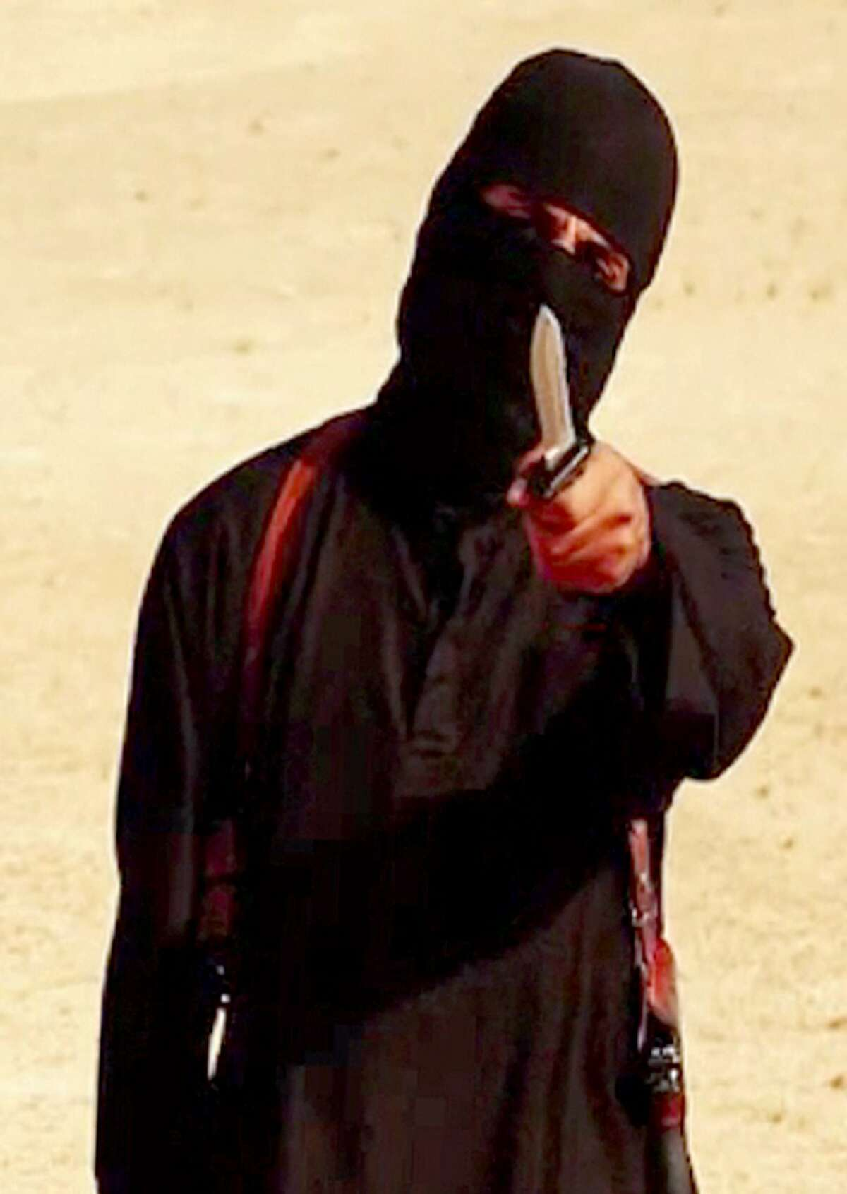 """A file image grab taken from a video released by the Islamic State (IS) and identified by SITE Intelligence Group on September 2, 2014 purportedly shows a masked militant holding a knife and gesturing as he speaks to the camera in a desert landscape before beheading 31-year-old US freelance writer Steven Sotloff. """"Jihadi John"""", the masked Islamic State militant apparently responsible for the beheading of western hostages including journalists James Foley and Steven Sotloff, was on February 26, 2015 named as London man Mohammed Emwazi by the Washington Post and the BBC. AFP PHOTO / SITE INTELLIGENCE GROUP / HO === RESTRICTED TO EDITORIAL USE - MANDATORY CREDIT """"AFP PHOTO / HO / SITE INTELLIGENCE GROUP - NO MARKETING NO ADVERTISING CAMPAIGNS - DISTRIBUTED AS A SERVICE TO CLIENTS FROM ALTERNATIVE SOURCES, AFP IS NOT RESPONSIBLE FOR ANY DIGITAL ALTERATIONS TO THE PICTURE'S ===HO/AFP/Getty Images"""