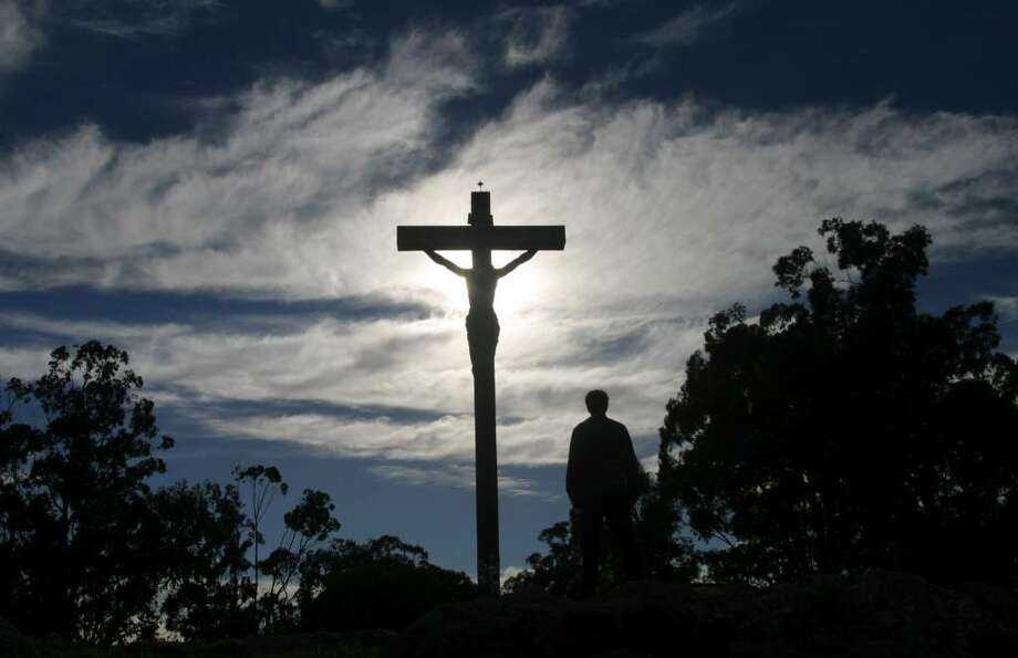 A man stands in front of a cross with an statue of Jesus Chirst during a Holy Week procession in Tandil, Argentina, Thursday, April 1, 2010. (AP Photo/Pablo Aneli) Photo: Pablo Aneli, AP / AP