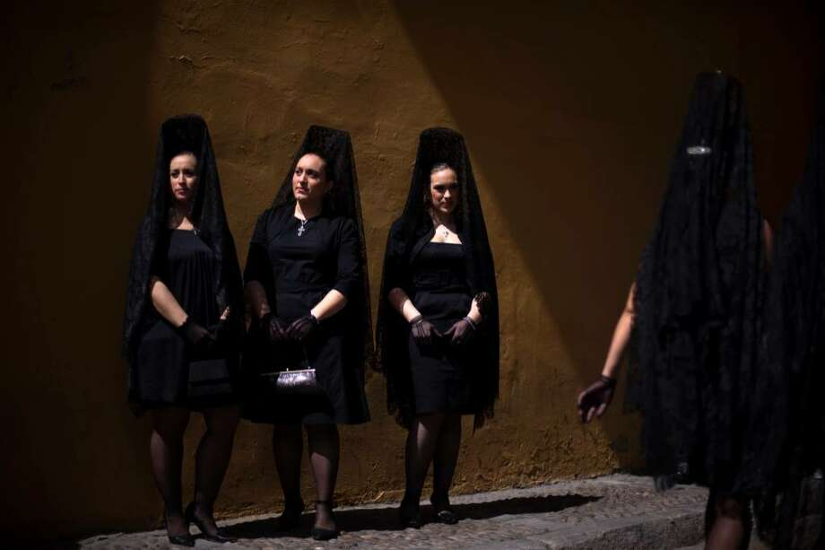 Women wearing the traditional mantilla pose for a photo at the entrance gate of La Macarena church before taking part in a procession during Holy Week in Seville, Spain,  Southern Spain, Thursday, April 1, 2010. (AP Photo/Emilio Morenatti) Photo: Emilio Morenatti, AP / AP