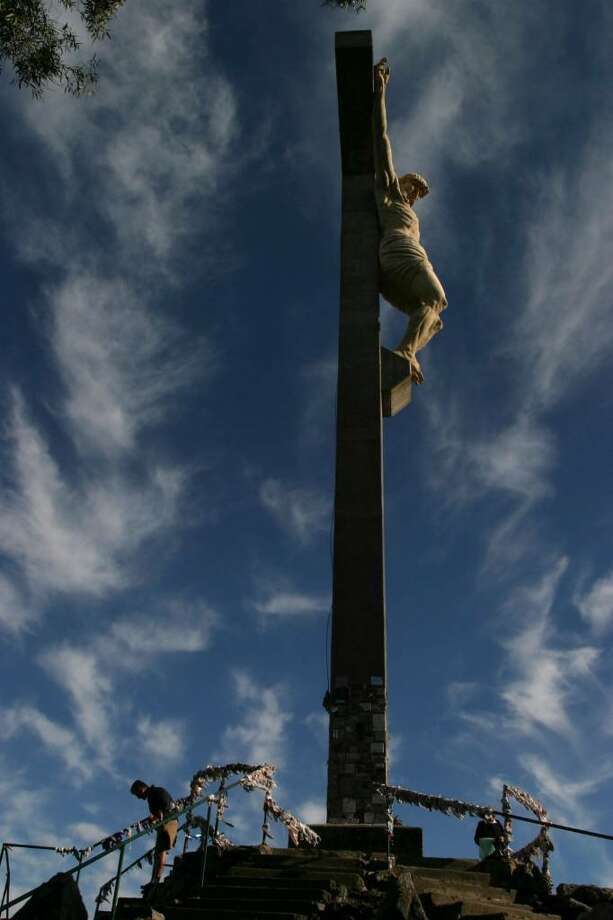 People walk past a cross with an statue of Jesus Christ during a Holy Week procession in Tandil, Argentina, Thursday, April 1, 2010. (AP Photo/Pablo Aneli) Photo: Pablo Aneli, AP / AP