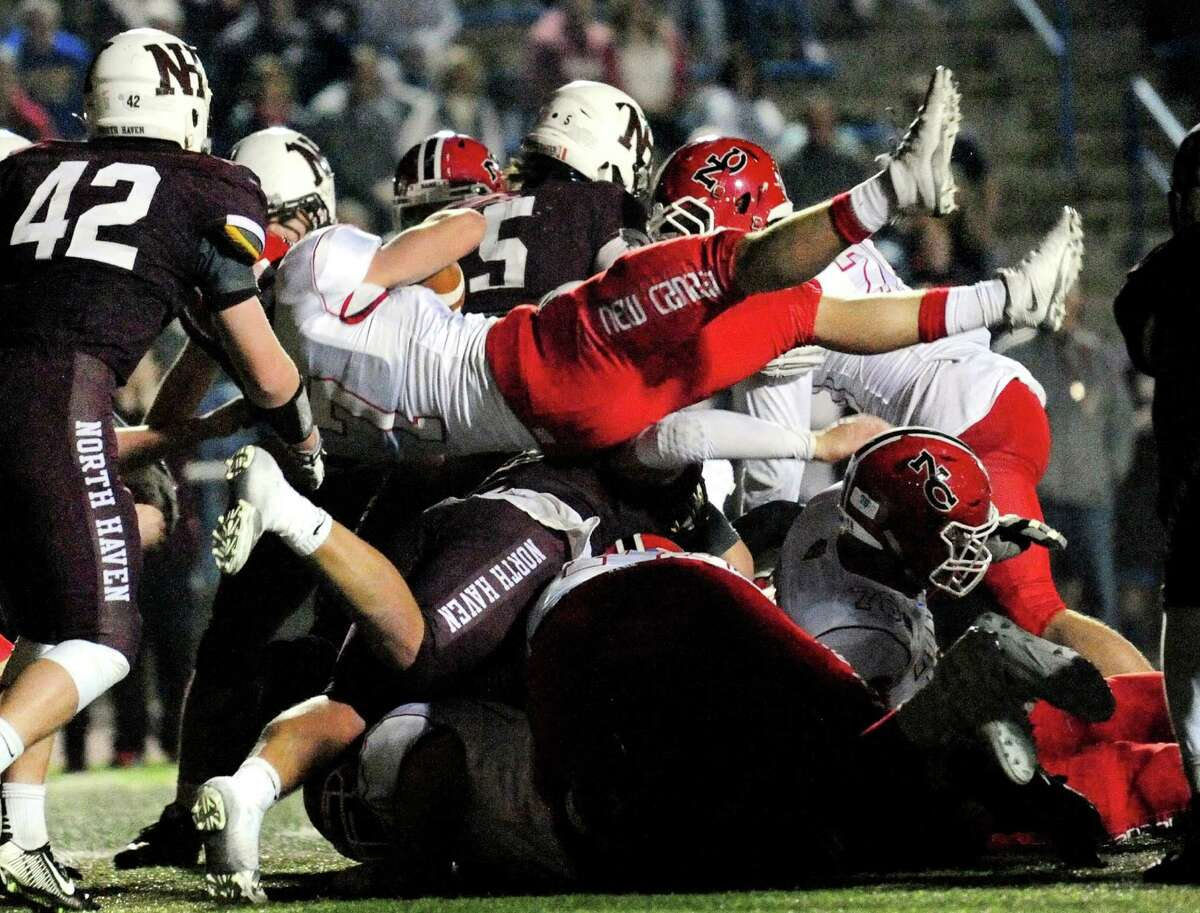 New Canaan's Ryan O'Connell leads over the pile and into the endzone to score a touchdown during Class L football championship action against North Haven in West Haven, Conn. on Saturday Dec. 12, 2015.