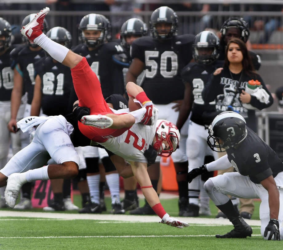 Katy receiver Jaxon Borowski (2) is tackled by defender Caden Sterns of Steele as as Sterns' teammate Isaiah Fields (3) looks on during fourth-quarter UIL Class 6A Division II state semifinal football action at Alamo Stadium on Saturday, Dec. 12, 2015 Photo: Billy Calzada, Staff / San Antonio Express-News / San Antonio Express-News