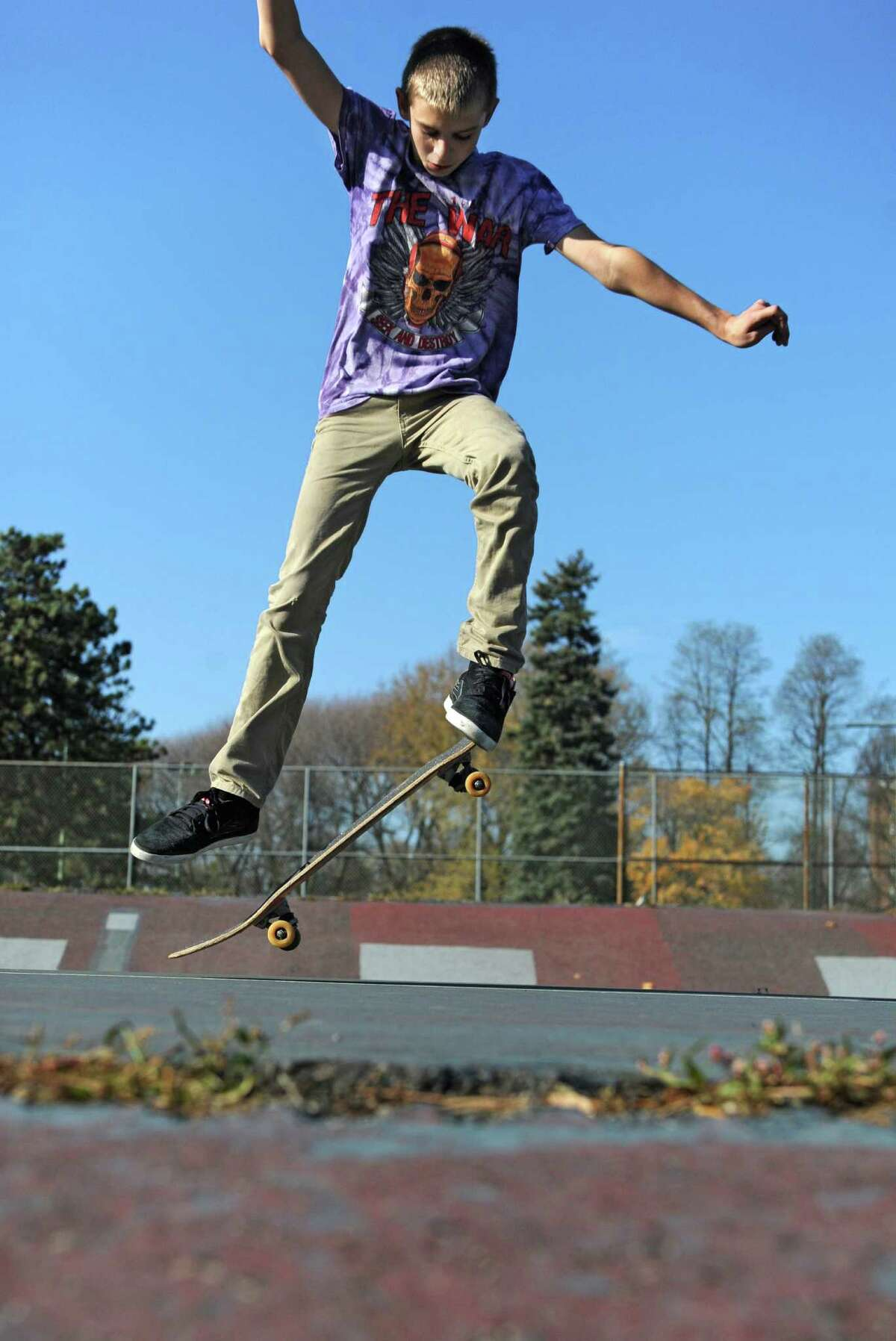 Skateboarder Dylan Allman, 14 of Ravena, works on his moves at the dilapidated tennis courts in Washington Park on Tuesday, Nov. 11, 2014 in Albany, N.Y. These four dilapidated tennis courts in Washington Park could become the city's first public skateboard park. The Recreation Department is soliciting public input on that possibility - as well as suggestions for other potential sites - starting Thursday night at a public session from 6 p.m. to 8 p.m. at Bleecker Stadium. (Lori Van Buren / Times Union) ORG XMIT: MER2015121114340929