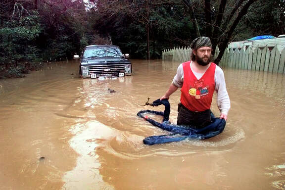 In the stormy winter of 1997-98, Ken Murray wades to rescue a truck from floodwaters on Neeley Road in Guerneville.