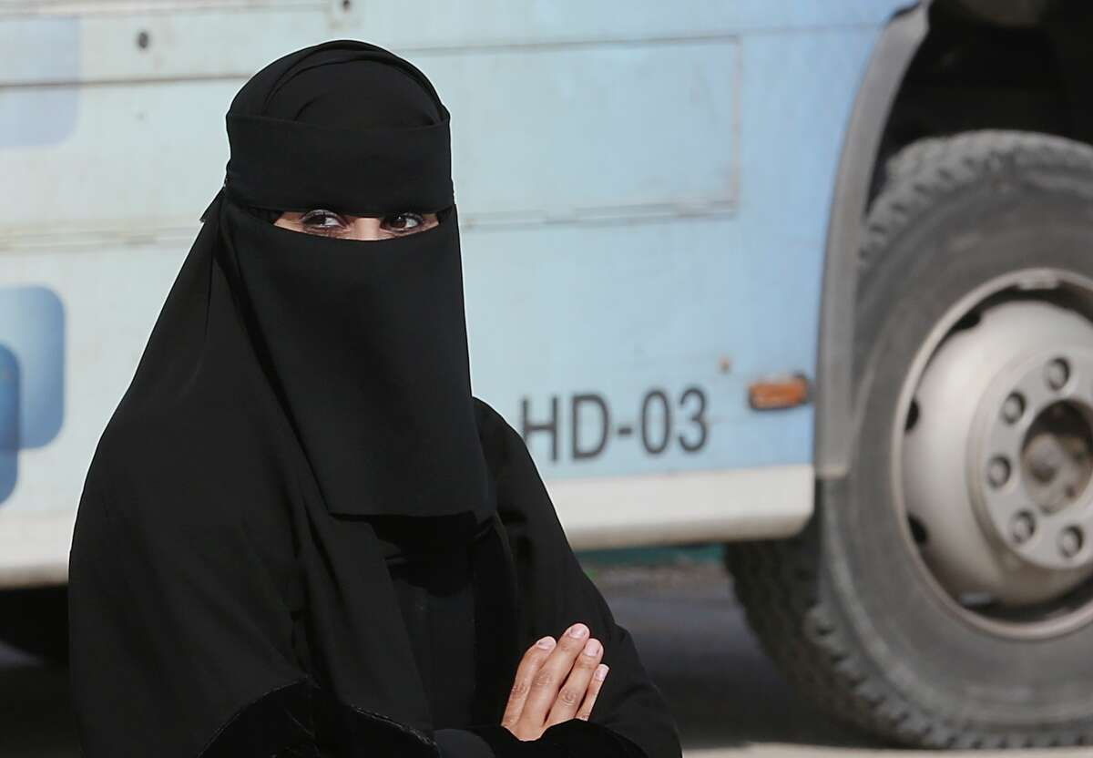 A Saudi woman waits outside a polling center as she prepares to cast her ballot during the country's municipal elections in Riyadh, Saudi Arabia, Saturday, Dec. 12, 2015. Women across Saudi Arabia marked a historic milestone on Saturday, both voting and running as candidates in government elections for the first time, but just outside polling stations they waited for male drivers ?- a reminder of the limitations still firmly in place. (AP Photo/Khalid Mohammed) ORG XMIT: BKM124
