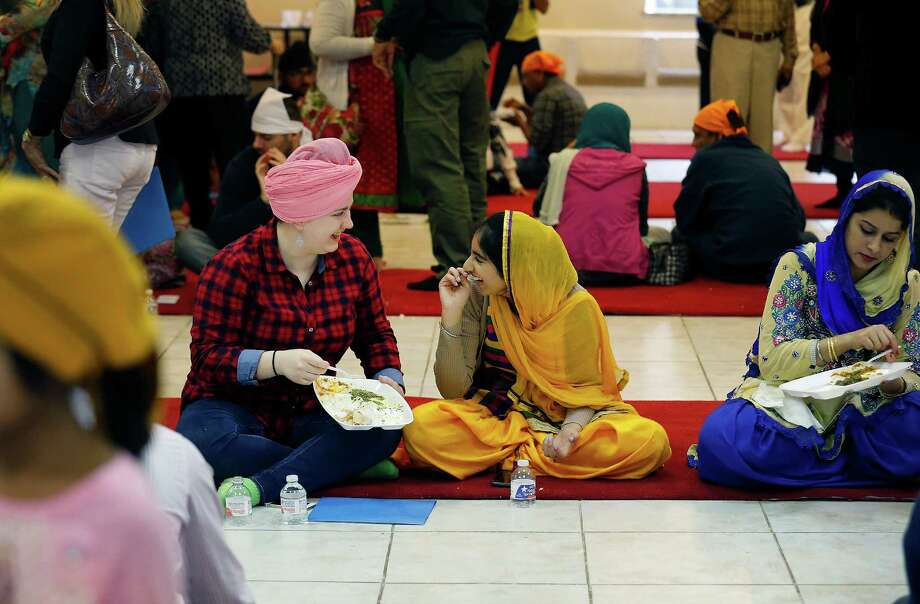 Sarah Trippy (left) and Shalbir Chatha join others for lunch at the Sikh Center's open house. Guests including Mayor Ivy Taylor, Police Chief William McManus and District 8 Councilman Ron Nirenberg joined the Sikhs' effort to strengthen interfaith relations. Photo: Photos By Kin Man Hui /San Antonio Express-News / ©2015 San Antonio Express-News