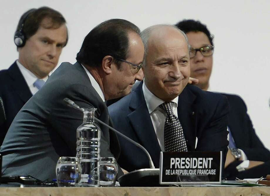 From left, French President Francois Hollande congratulates French Foreign Minister Laurent Fabius, the president of the conference. The accord Fabius brokered is a landmark sought by environmentalists for decades. Photo: MIGUEL MEDINA, Staff / MIGUEL MEDINA