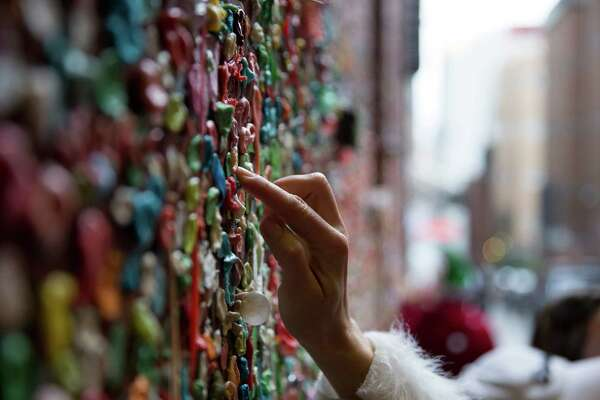 A woman places a piece of gum on the recently restored Gum Wall during SantaCon in downtown Seattle on Saturday, Dec. 12, 2015.