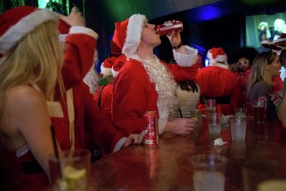 Santa Claus finishes his tallboy at Club Contour during SantaCon in Seattle on Saturday, Dec. 12, 2015.