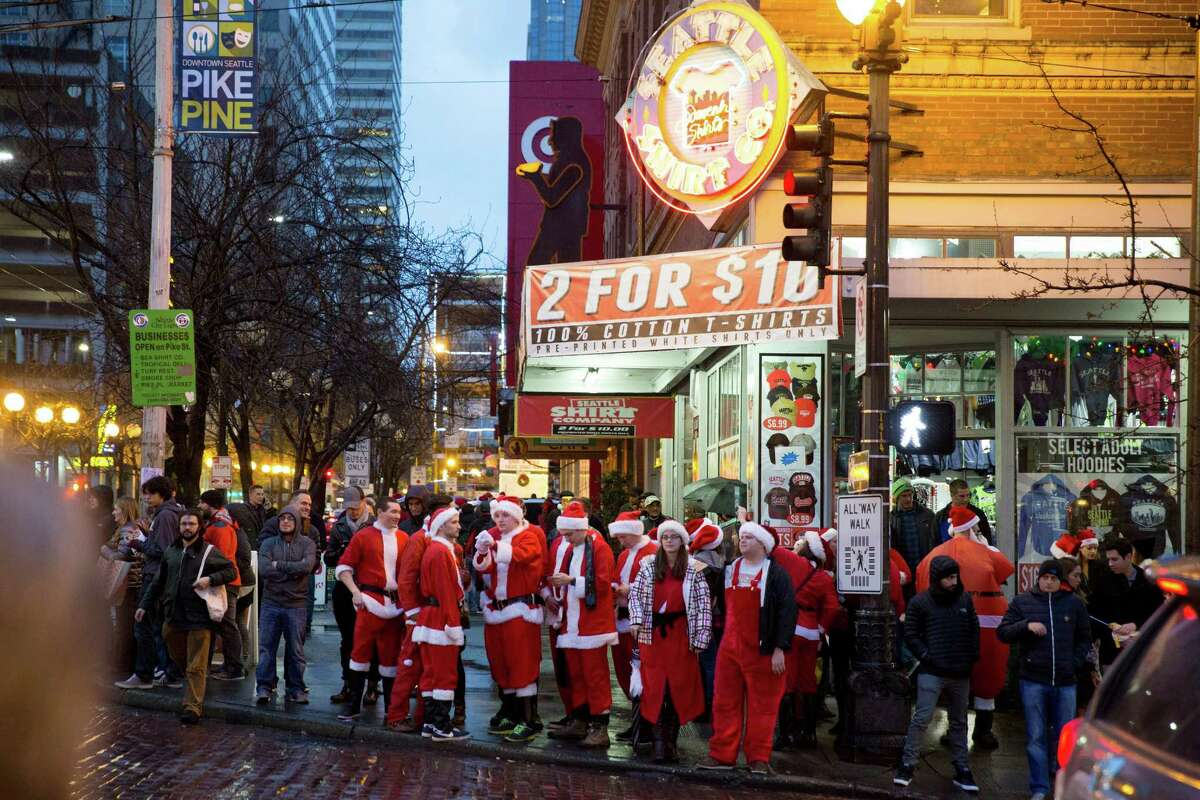 A group of Santa Clauses cross First Avenue.