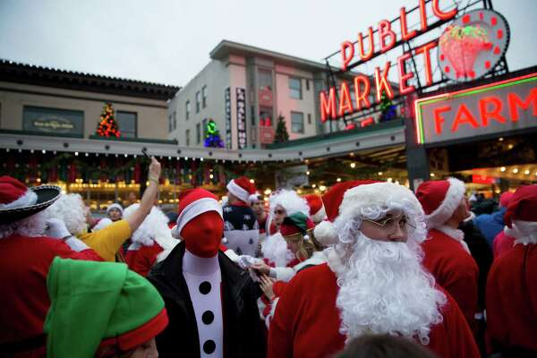 SantaCon attendees mill about while waiting for a group photo at Pike's Place in downtown Seattle on Saturday, Dec. 12, 2015.