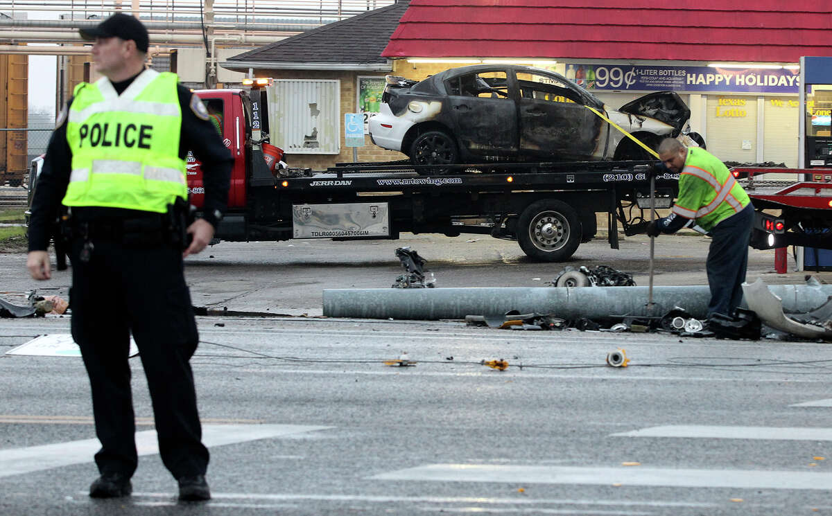 A wrecker driver (right) cleans up by a burned vehicle that slammed into a pole about 3:30 a.m. Thursday December 11, 2014 at FM 78 and Ackerman in Kirby. The driver of the vehicle died at the scene.