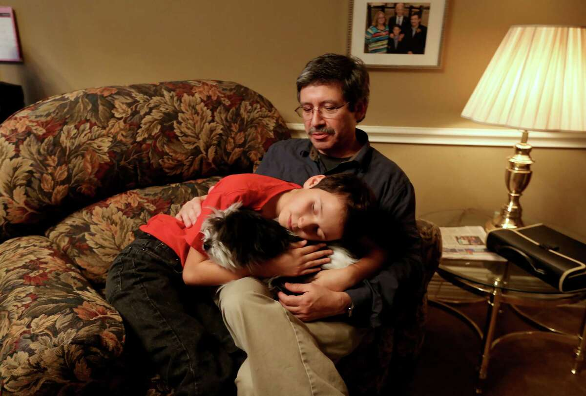 Benjamin Elder, 10, who identifies as a gender different than the one assigned at birth based on his anatomy, a female, with father Jim Elder and his dog Pepper at their home Wednesday, Nov. 18, 2015, in Friendswood, Texas. Ben was born Nov. 1, 2005 with the given name Marissa. Ann and husband Jim Elder adopted Benjamin as an infant. Before entering the first grade, he transitioned from a female to a male having his name and gender legally changed in court.