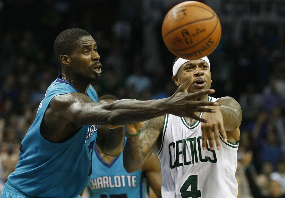 Celtics guard Isaiah Thomas (right), who had 13 assists, zips a pass past Hornets forward Marvin Williams. Photo: Nell Redmond, Associated Press