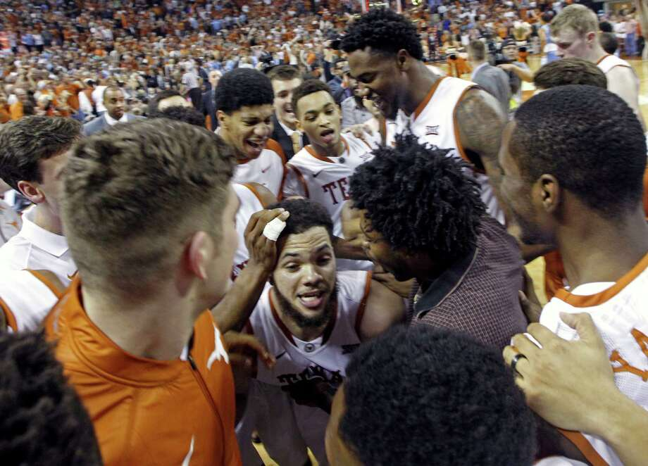 Texas senior guard Javan Felix, center, is swarmed by teammates after making a last-second shot Saturday to upset No. 3 North Carolina. Felix had 25 points. Photo: Michael Thomas, FRE / FR65778 AP