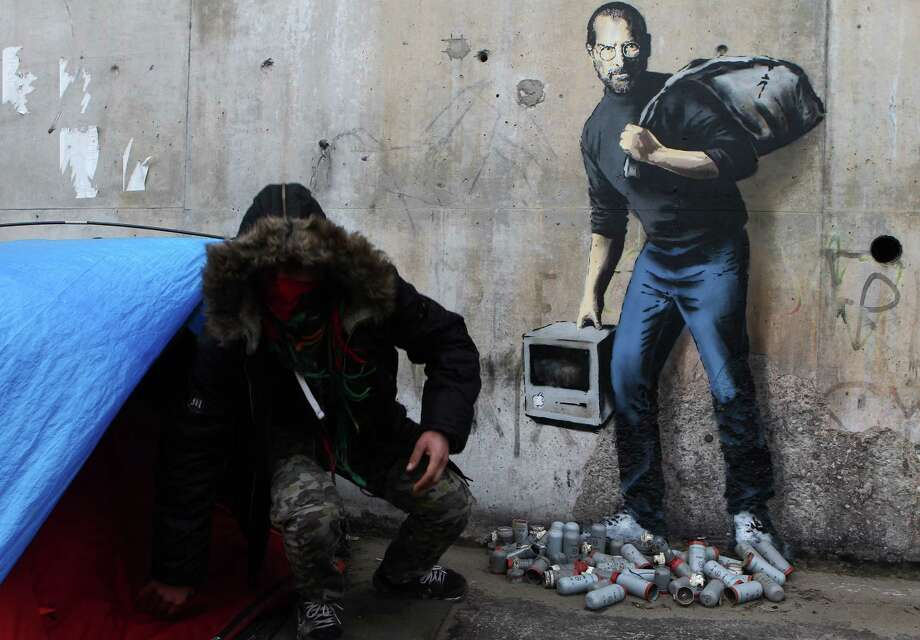 A painting by English graffiti artist Banksy at the entrance of the Calais refugee camp in France depicts Steve Jobs, whose father was from Syria. Photo: Michel Spingler, STR / AP