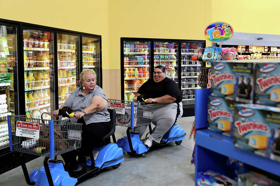 Hector Garcia Jr. and his mother, Elena Garcia, grocery shop near their home in San Antonio on June 14, 2014. Hector passed away on Dec. 8, 2014 after a lifelong battle with obesity. Elena made a promise to her son to lose weight and since his death she has lost 50 pounds and no longer needs the electric cart for shopping. Photo: Lisa Krantz / Staff