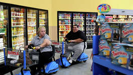 Hector Garcia Jr. and his mother, Elena Garcia, grocery shop near their home in San Antonio on June 14, 2014. Hector passed away on Dec. 8, 2014 after a lifelong battle with obesity. Elena made a promise to her son to lose weight and since his death she has lost 50 pounds and no longer needs the electric cart for shopping.