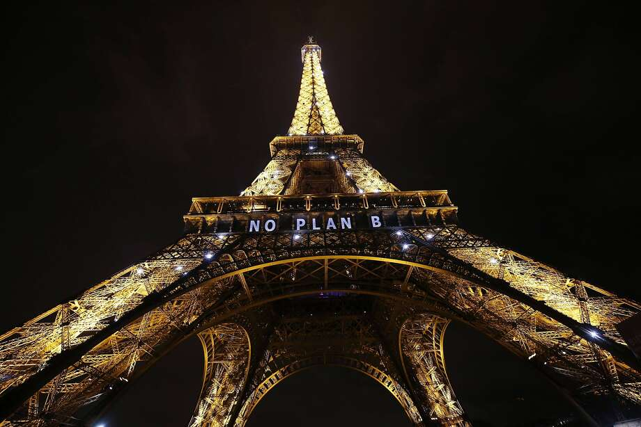 """TOPSHOT - The Eiffel Tower displays the message """"No plan B"""" within the United Nations Climate Conference on Climate Change, on December 11, 2015 in Paris.  World powers led a frenetic final push on December 11 to seal a UN accord aimed at averting catastrophic climate change, as sleep-deprived envoys battled in Paris over trillion-dollar disputes blocking a deal. / AFP / PATRICK KOVARIKPATRICK KOVARIK/AFP/Getty Images Photo: Patrick Kovarik, AFP / Getty Images"""