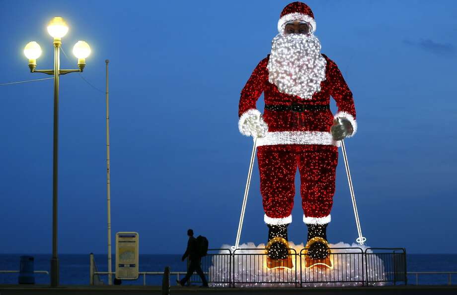 """TOPSHOT - A giant illuminated Santa Claus model is displayed along the """"Promenade des Anglais"""" in the French Riviera city of Nice, southeastern France, on December 12, 2015.  / AFP / VALERY HACHEVALERY HACHE/AFP/Getty Images Photo: Valery Hache, AFP / Getty Images"""