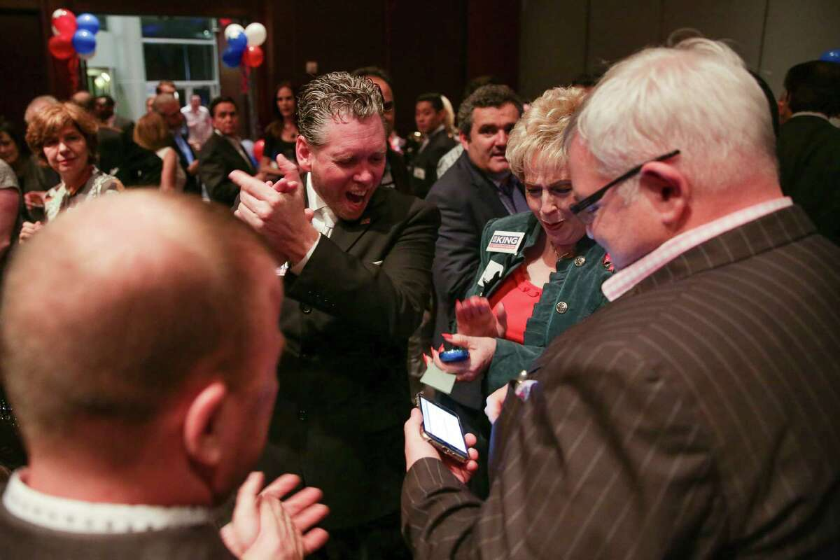 Tex Christopher, center, cheers at the election party for mayoral candidate Bill King as King gains on Sylvester Turner's early lead Saturday, Dec. 12, 2015, at the Royal Sonesta Hotel in Houston.