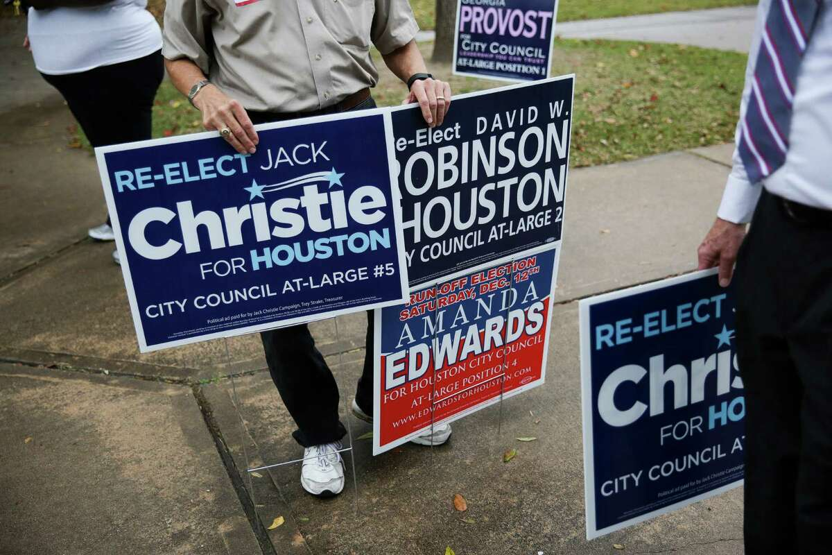 Edwin Friedrichs displays campaign signs as he engages voters outside Poe Elementary School in the final hours of Houston's runoff election Saturday.