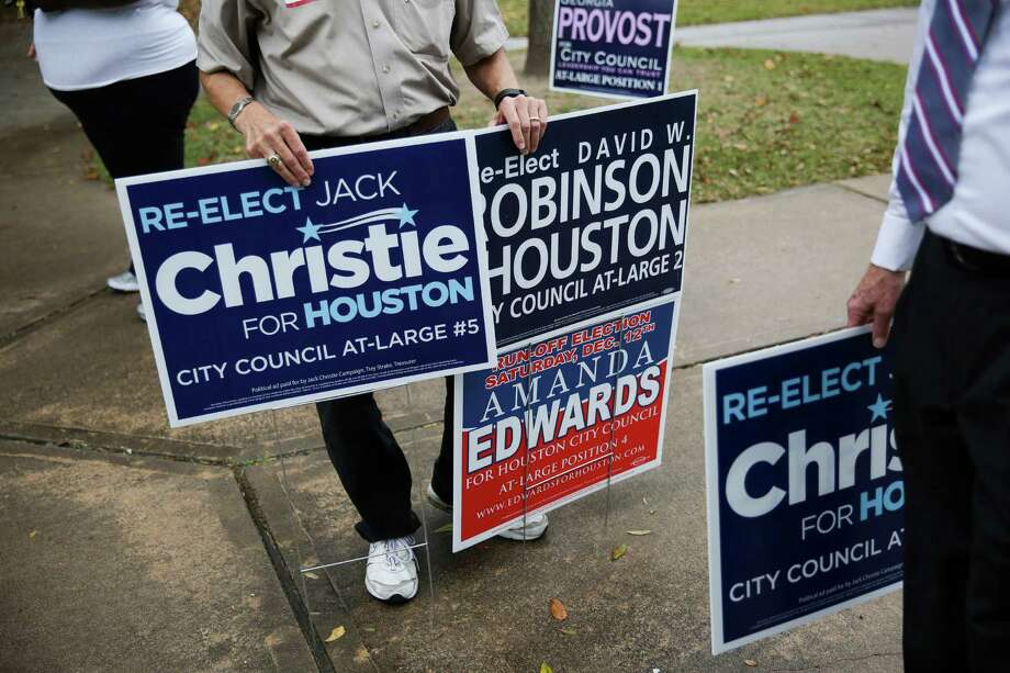 Edwin Friedrichs displays campaign signs as he engages voters outside Poe Elementary School in the final hours of Houston's runoff election Saturday.  Photo: Michael Ciaglo, Staff / © 2015  Houston Chronicle