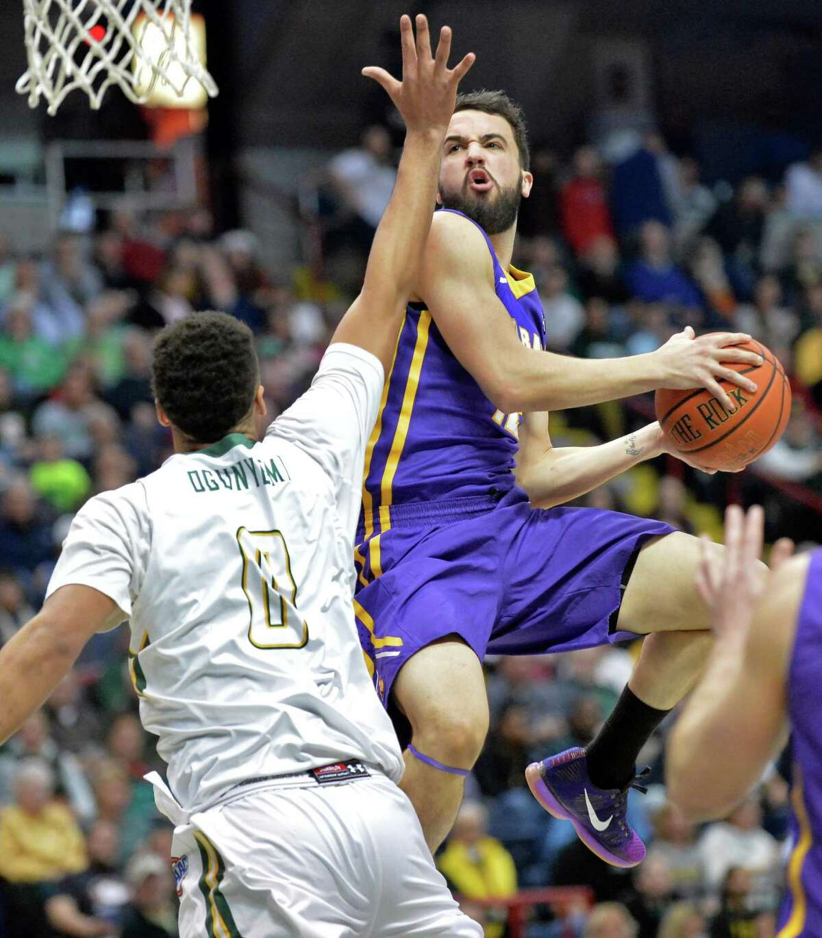 UAlbany's #12 Peter Hooley gets to the basket over Siena's #0 Javion Ogunyemi, left, during Saturday's game at the Times Union Center Dec. 12, 2015 in Albany, NY. (John Carl D'Annibale / Times Union)