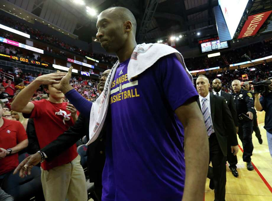 The Lakers' Kobe Bryant high-fives fans as he leaves the court at Toyota Center following his team's 126-97 loss to the Rockets on Saturday night. Photo: Elizabeth Conley, Staff / © 2015 Houston Chronicle