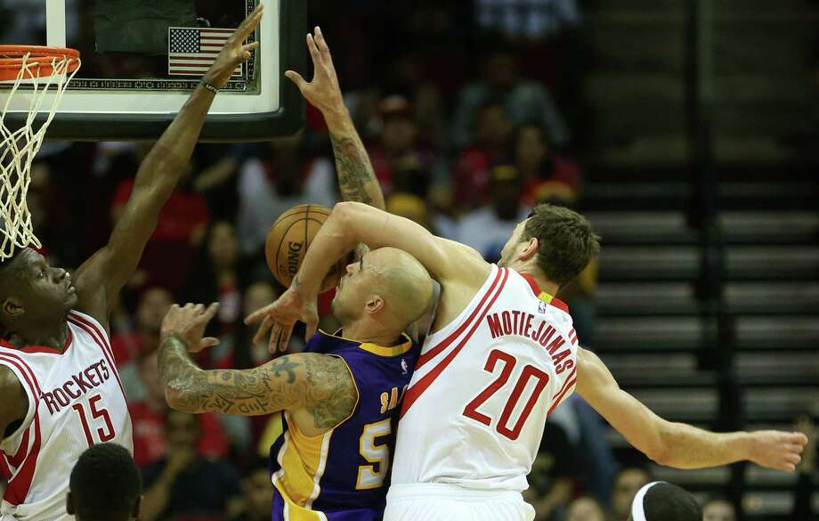 Rockets forward Donatas Motiejunas, right, makes Lakers center Robert Sacre aware of his presence by virtue of a second-half foul Saturday night. Photo: Elizabeth Conley, Staff / © 2015 Houston Chronicle