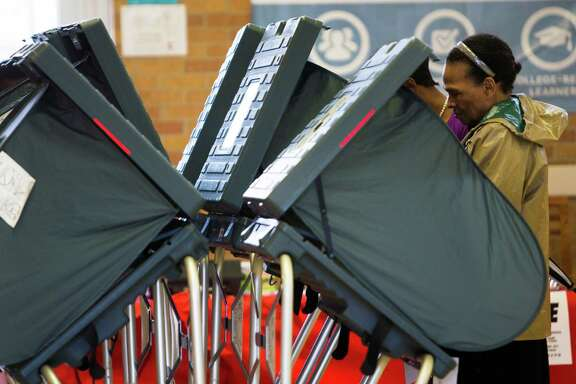 A voter cast her vote at the J.G Osborne Elementary School precinct 197. By 11:30 a.m., 113 voters had shown on the poll at Osborne, Saturday, Dec. 12, 2015, in Houston.