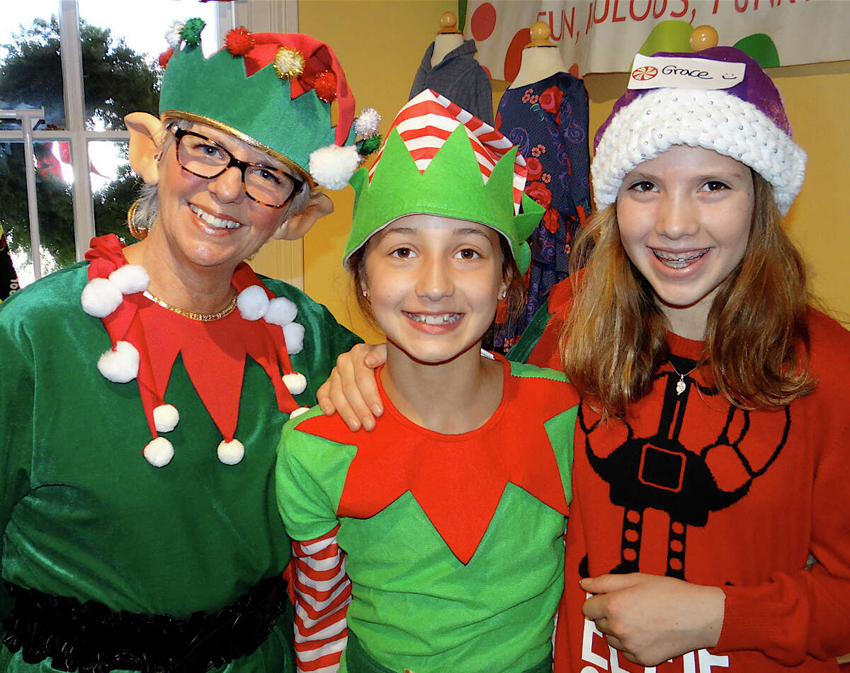 Volunteer Santa's helpers Cheryl Logsdon, Grace Beccaria and Grace Davidson greet visitors to the Burr Homestead for