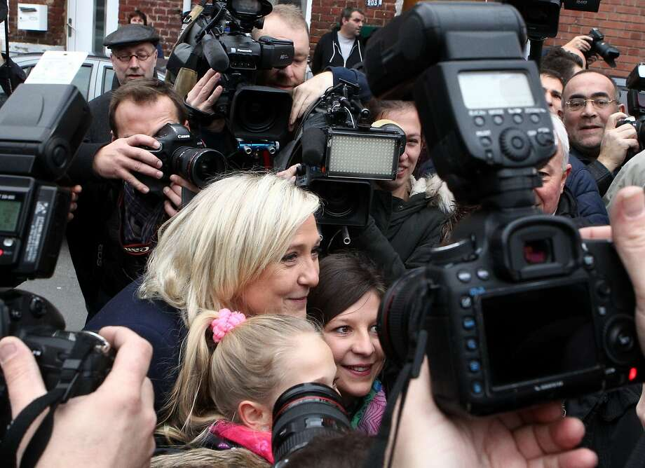 National Front party leader Marine Le Pen (center) poses for pictures outside her polling station. Photo: Michel Spingler, Associated Press